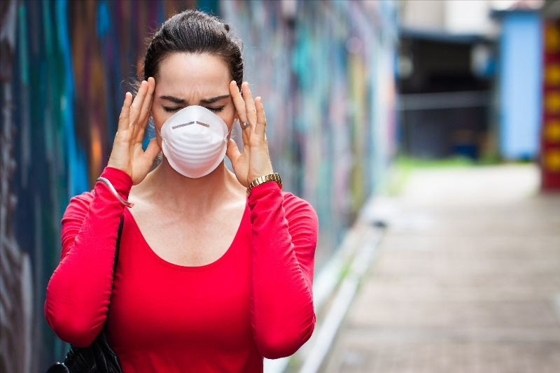 women in a red shirt with a face mask and hands on head
